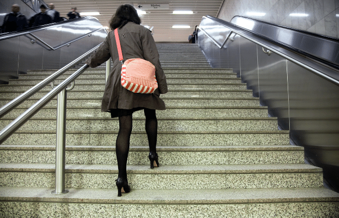 woman taking the stairs instead of the escalator for more exercise