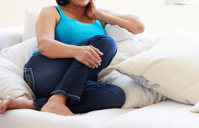 overweight woman in blue shirt and jeans sitting on sofa