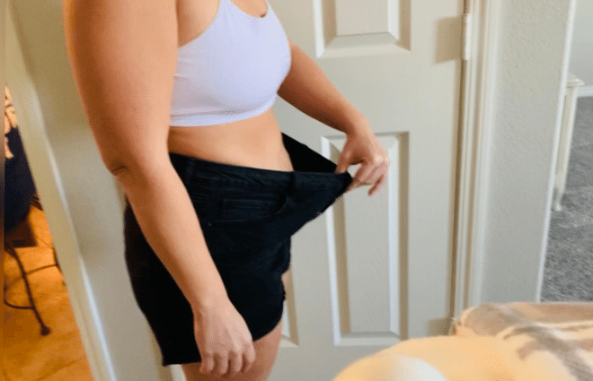 Chrystal in sports bra and old, loose workout shorts, holding waistband of shorts out to show how much weight and girth she has lost.