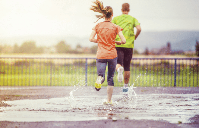 Man and woman running in the rain and big puddle